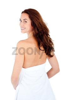 Radiant caucasian woman with a towel on her body smiling at the camera against a white background
