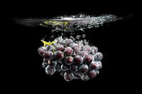 Isolated Red grapes splashing and sinking in water on black