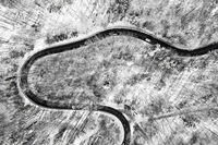 Aerial view at a curvy road as topdown shot in the winter with the street surrounded by the white clean snow.