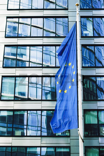 European Union flag waving in front of modern corporate office building, symbol of EU Parliament, Commission and Council