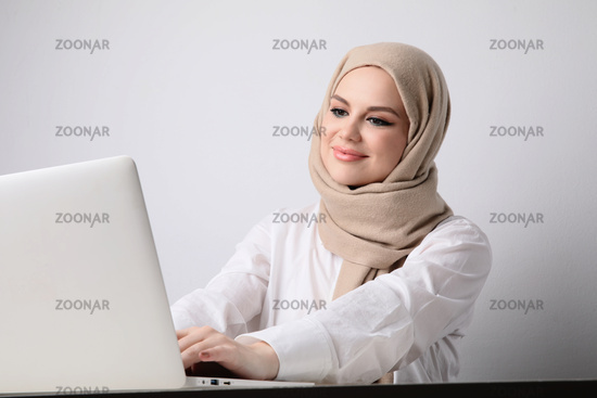 Portrait of young happy muslim woman working with laptop. Isolated.