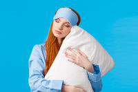 Beauty, female and lifestyle concept. Relaxed and relieved lovely redhead woman in sleep mask and pyjama, close eyes sleepy, having sweet dreams, hugging pillow, standing blue background