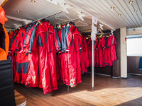 Row of red survival suits on hangers