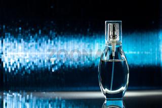 Bottle of perfume on blue background
