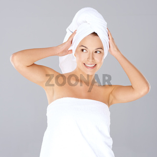 Vivacious woman wrapped in white towels