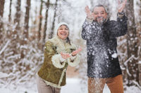 Happy playful mature family couple sledding in winter park, laughing and having fun together
