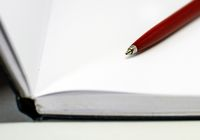 Red ballpoint pen on the blank white pages of an open notebook