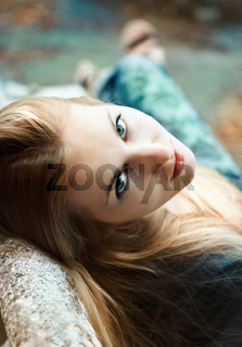 Young blond girl in autumn park in the evening