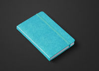 Aqua blue closed notebook isolated on black