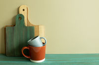 Mug cup and wooden tray, cutting board on green wooden table. khaki wall background. kitchen interior