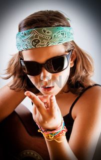 Pre-teen girl with acoustic guitar wearing sunglasses and bandanna and making peace/ victory sign.