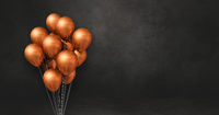 Copper balloons bunch on a black wall background. Horizontal banner.