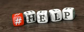 Roter Hashtag-Würfel und weiße Buchstaben-Würfel mit dem Wort 'HELP' auf Holzuntergrund
