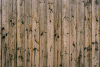 The texture of dark wooden planks knocked down in an upright position of brown color close-up.
