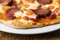 Salami-Pizza auf dunklem Holz
