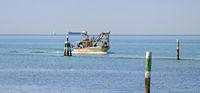 fishing ship on homeward journey between waterway marks