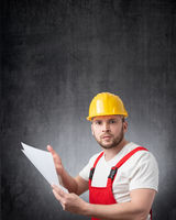 An angry construction worker holding papers or documents