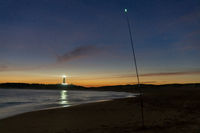 A fishing rod with luminescent tip on a beach at night with lighthouse behind