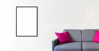Empty picture frame on a white wall above a sofa. Horizontal banner
