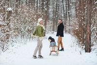Happy family walking in winter forest