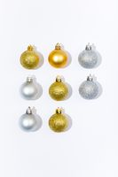 Composition of three gold and silver baubles on white background