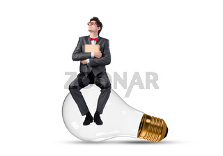A young businessman sits on a light bulb