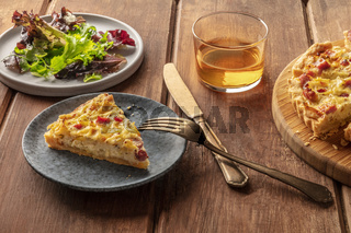 A French dinner. A slice of a quiche lorraine with mesclun leaves and white wine on a rustic wooden background