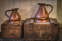 Vintage copper jugs standing on wooden crates with Bushmills whiskey bandings
