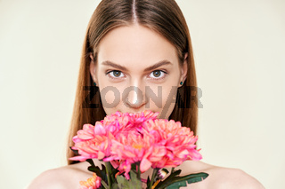 Portrait of beautiful young woman with flowers on studio background