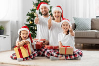 happy family sitting under christmas tree at home