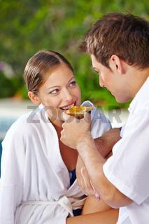 Frau isst Toast am Pool