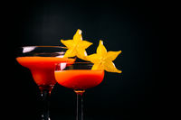 Red cocktail decorated with starfruit on black background.