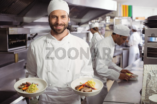 Smiling chef holding delicious dish in kitchen