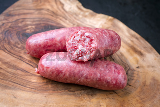Traditional Italian raw salsiccia fresco meat sausage offered as close-up on a rustic wooden cutting board