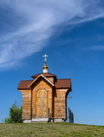 Small old wooden chapel on summer green grassy hill top, and blue sky with cloud.