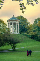 A happy couple is walking right to the Monopteros temple in Munichs green, Englischer Garden, enjoying their romantic time together.
