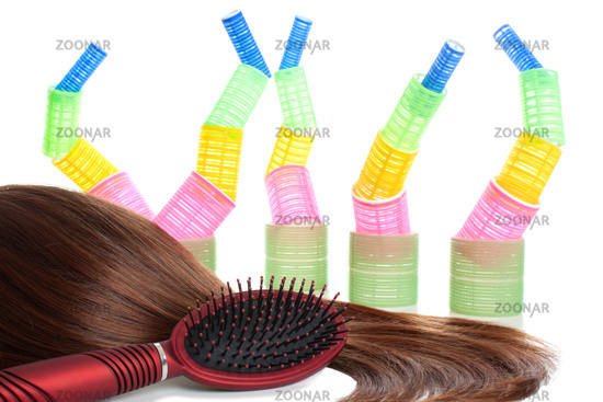 Brown hair, comb and hair curlers   Isolated