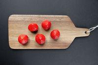 Strawberries on a cutting board. Black background