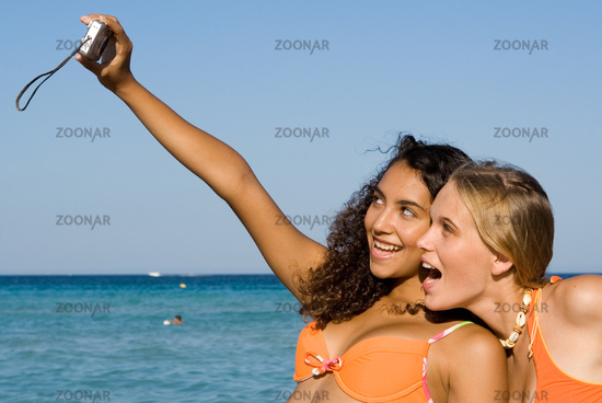 young people taking photos with camera at beach