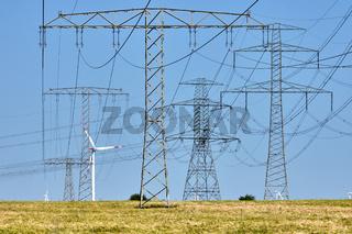 Strommasten und Stromleitungen mit Windkraftanlagen im Hintergrund