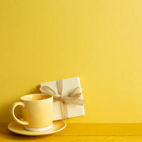 Gift box and coffee cup on wooden table. yellow wall background
