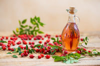 Rosehip oil in glass bottle on wooden table horizontal