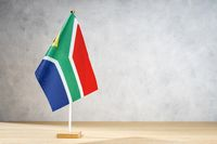 South Africa table flag on white textured wall. Copy space for text, designs or drawings