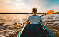 Young girl in a kayak paddling on the lake at sunset - view from behind her back