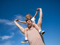 Little girl sit on neck of father