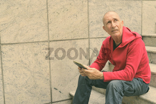 Bald senior man thinking and looking up while holding digital tablet on the staircase against concrete wall