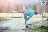 Sporty young woman is stretching for warmup, jogging
