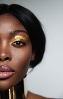 Cropped headshot of young black woman with natural skin, posing in the studio.