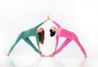 Two young women doing yoga indoor, standing in position isolated over white studio background