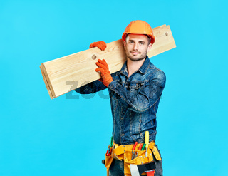 Young handsome carpenter hold lumber on his shoulders over blue background